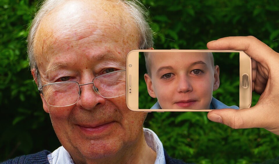 Phone with an image of a child on the camera, pointed at an old man.  Inferring the old man looks younger on the phone's camera