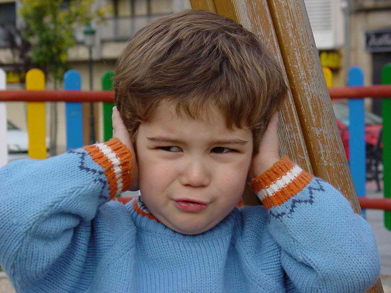 Toddler making a face and covering his ears