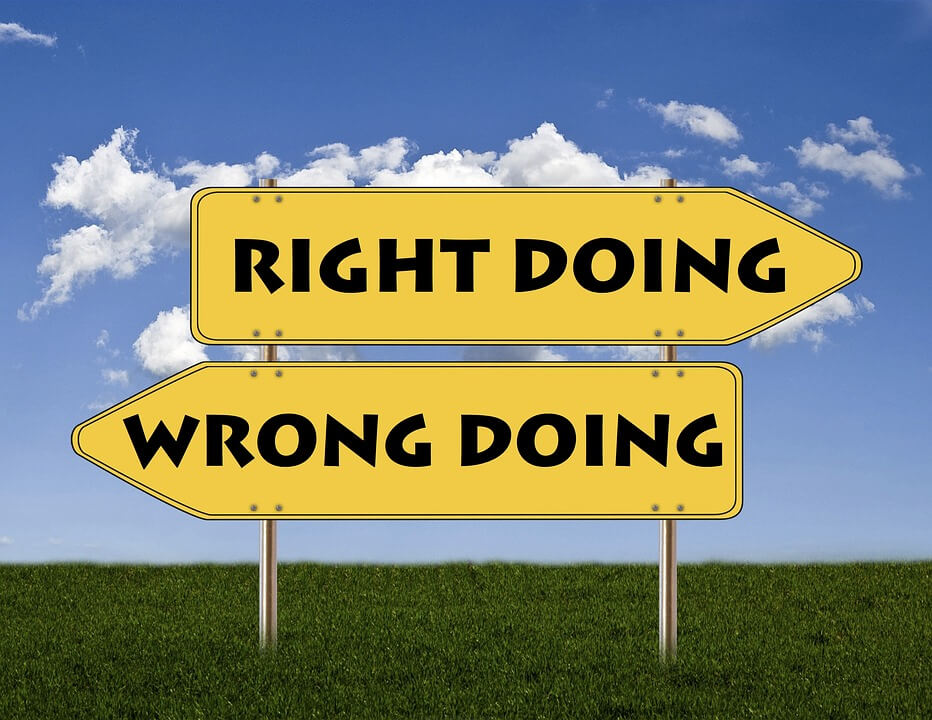 """Signs pointing different directions one says """"right doing"""" and one says """"wrong doing"""""""