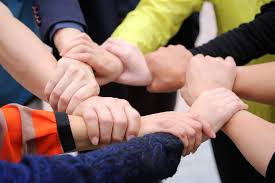 People holding hands to wrist in a circle formation, unity