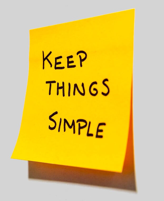 """When considering the importance of records keeping, simplifying your organizational style is also important. Yellow sticky note stuck to a wall with """"keep things simple"""" written on it in black marker."""