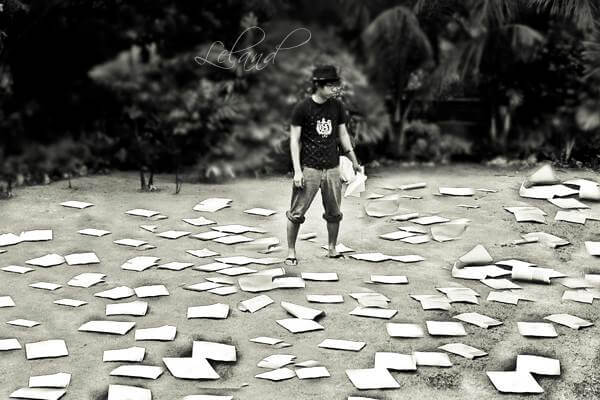 Papers spread out all over the ground, man standing in the middle of papers looking perplexed