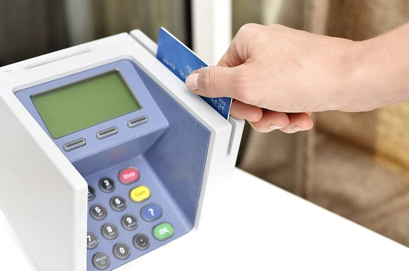 Someone swiping a credit card through a credit card reader.
