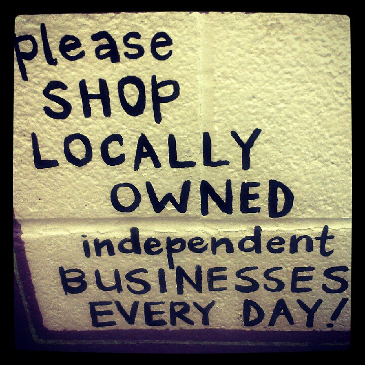 """Shop local graffiti on a brick wall, says, """"Please shop locally owned independent businesses every day!"""""""
