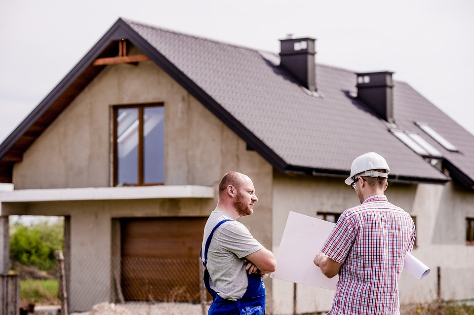 Local contractor showing house plans to a man in front of his home