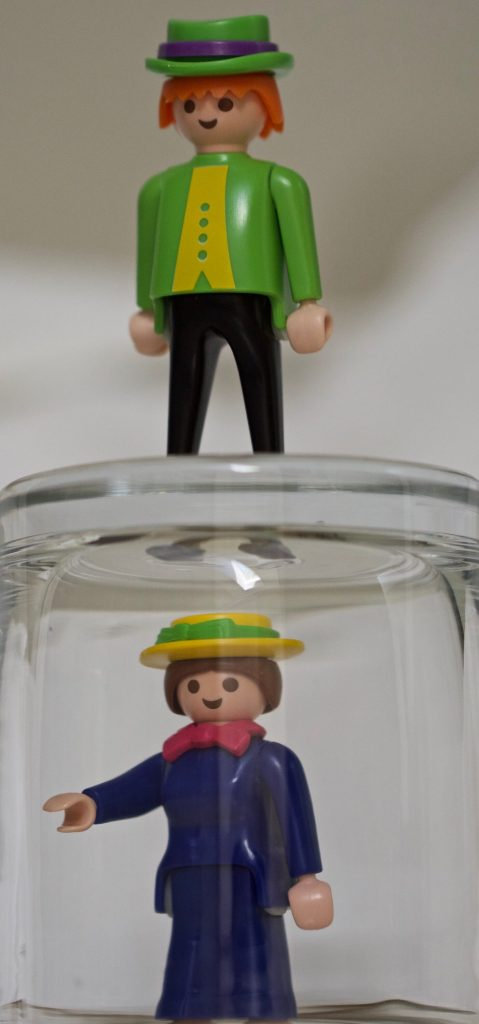 A toy man stands over a toy woman who is trapped under a glass.