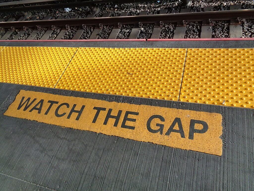 """The words """"WATCH THE GAP"""" highlighted in yellow next to the gap near railroad tracks."""