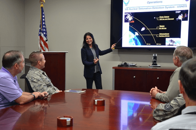 A professional woman giving a presentation to a group of men.