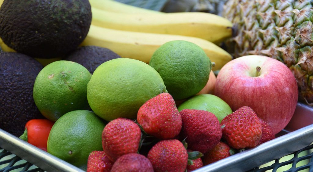 Photo of produce, including limes strawberries, avocados, bananas, apples, and pineapple sitting in a metal pan on a wrought iron table.