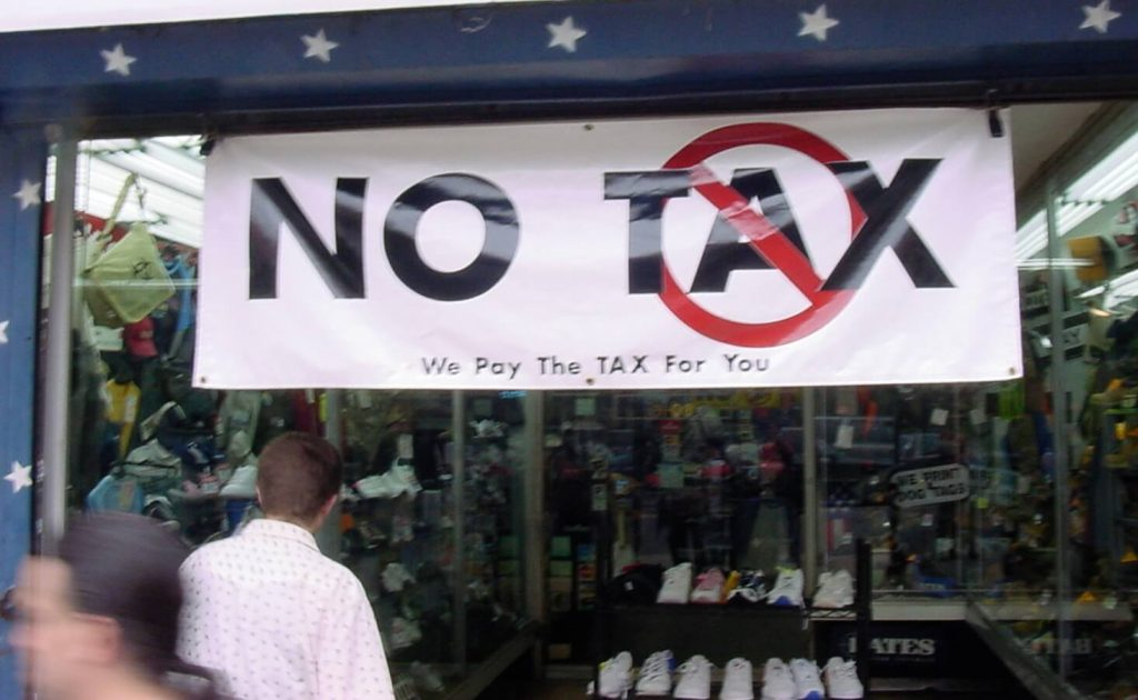 """Photo of a sign saying, """"NO TAX, We Pay The TAX for You,"""" with people walking by."""