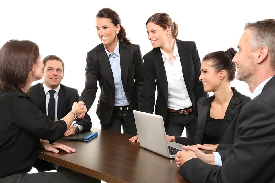 Photo of a group of business people shaking hands and smiling around at table.