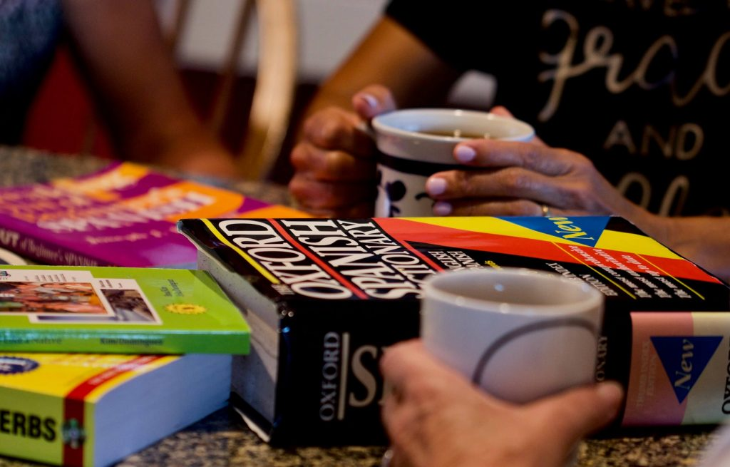 Photo of people sitting around a table with coffee mugs in their hands, and language books sitting in the middle of the table.