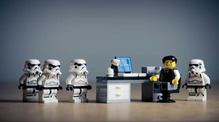 Lego figurines, figure working at desk with storm troopers bullying him