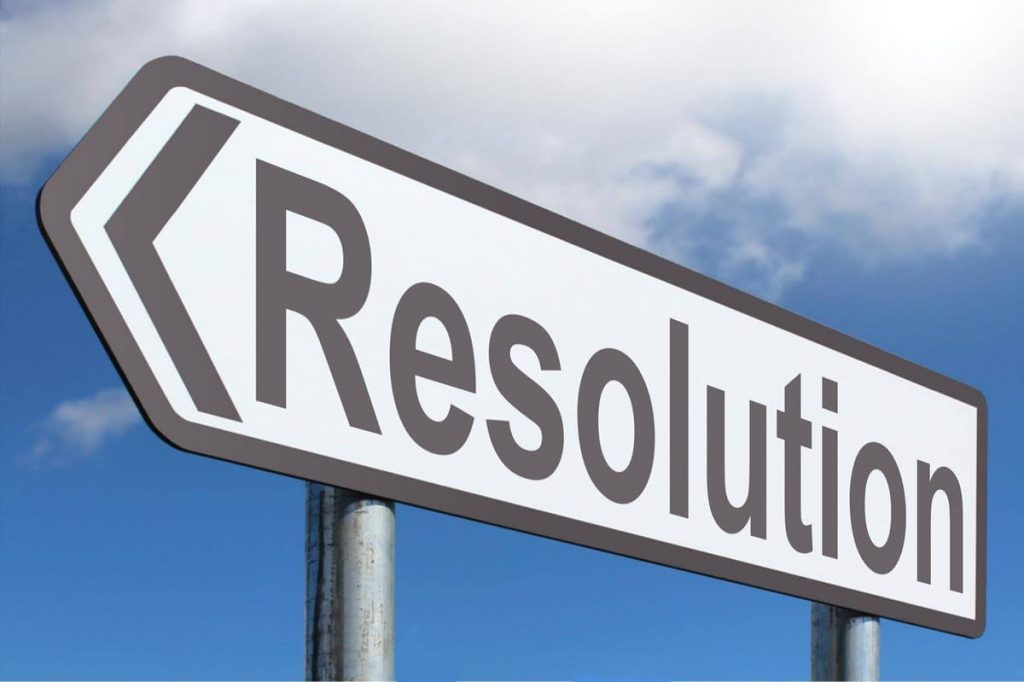 """Road sign in front of a blue sky that says """"resolution"""""""