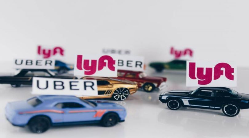 Image of mini cars with Uber and Lyft signs over them.