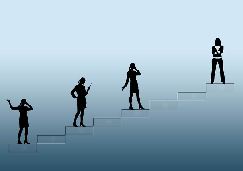Image of women trying to climb the corporate ladder, relating to diversity in the workplace.