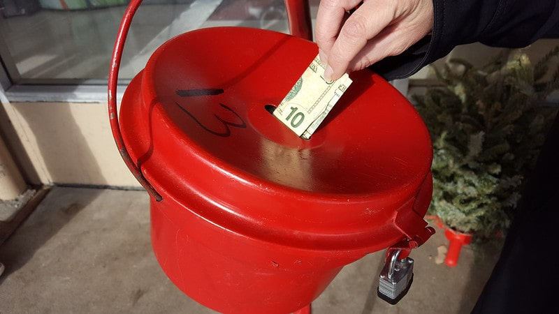 Photo of a red donations bucket with someone putting a $10 bill through the slot.