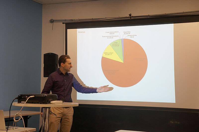 Photo of man presenting data related to donations.
