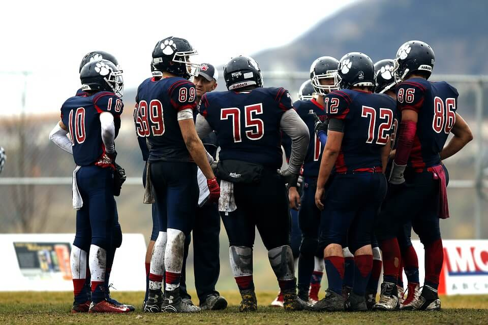 Photo of football players in a huddle.
