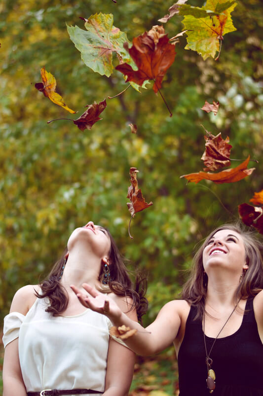 Image of two women throwing leaves in the air, smiling because they are going green.