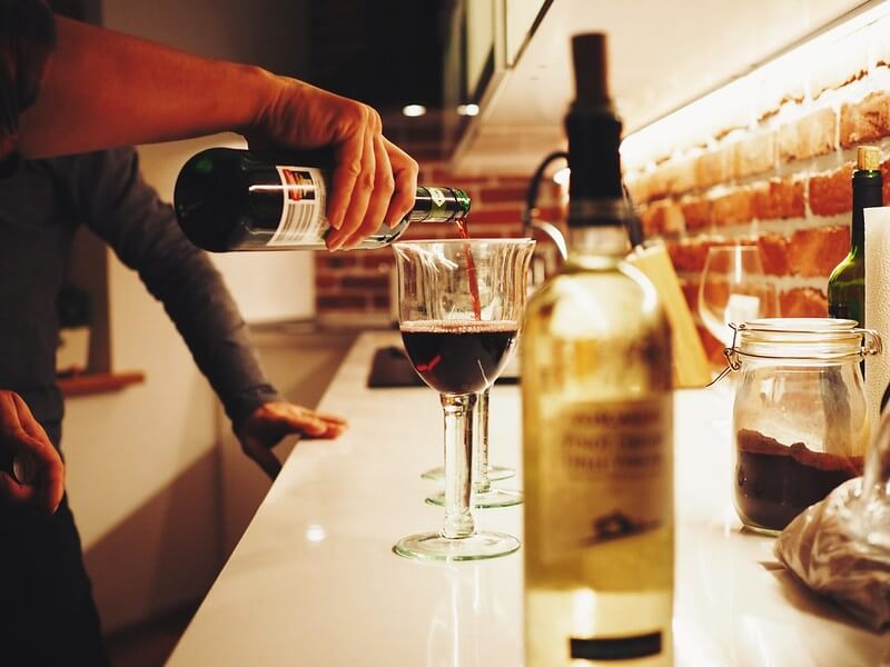 Image of hand pouring a glass of wine, as a company wines and dines clients, meanwhile receiving a tax deduction for the event.