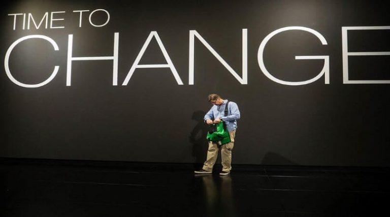 """Photo of a man looking into a green bag with the words """"Time to Change"""" typed above him on the wall."""