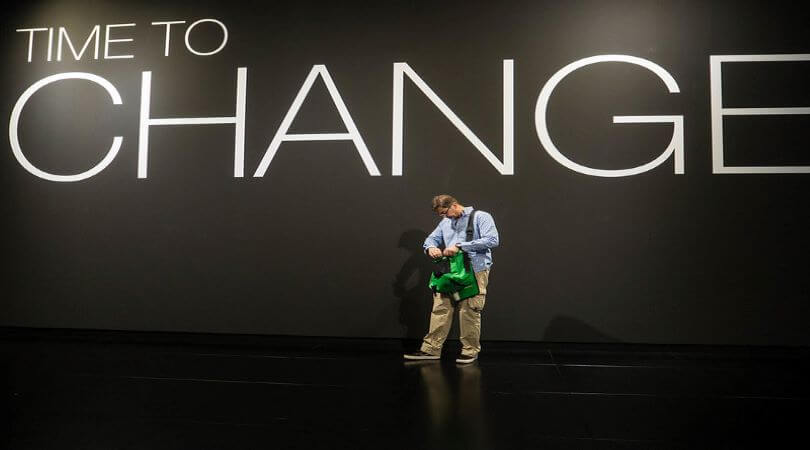 "Photo of a man looking into a green bag with the words ""Time to Change"" typed above him on the wall."