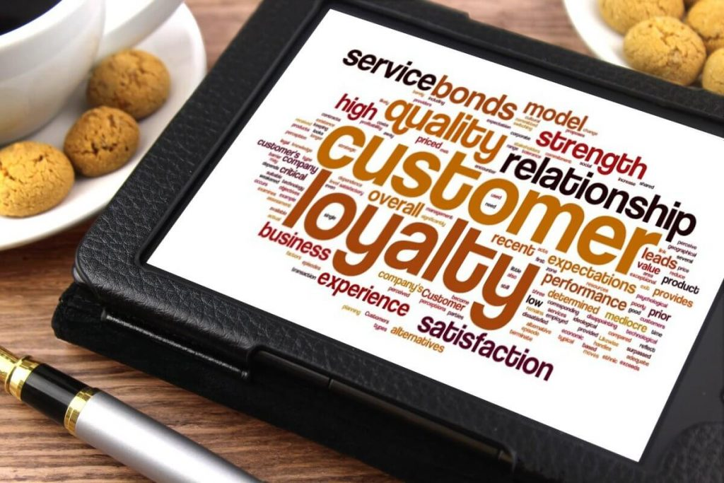 Photo of a tablet with a collage of words related to customer loyalty.