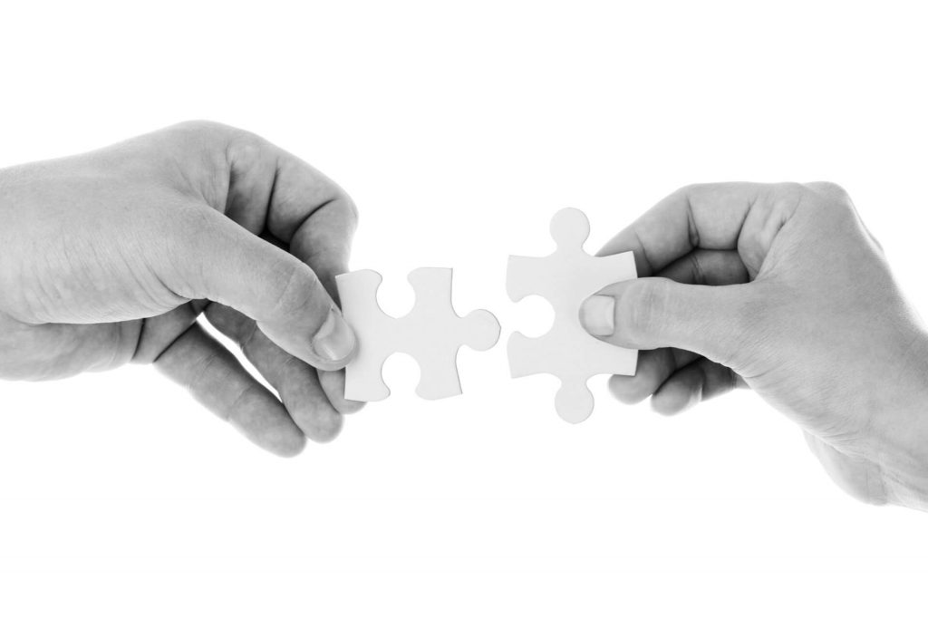 A picture of two hands placing two pieces of a puzzle together, indicating employee matching.