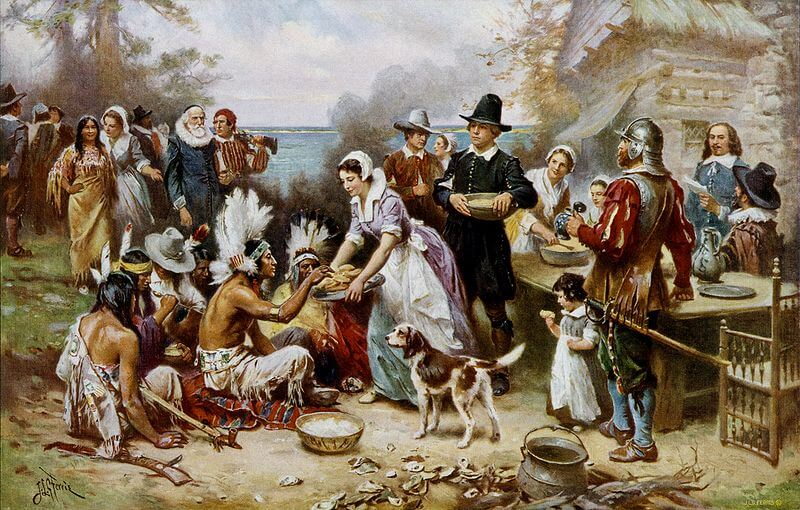 Image of Pilgrims and Native Americans sharing what appears to be the first Thanksgiving feast.