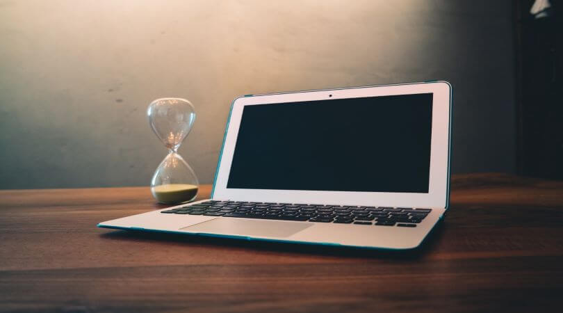 Photo of an hourglass sitting on a computer representing a deadline extension.