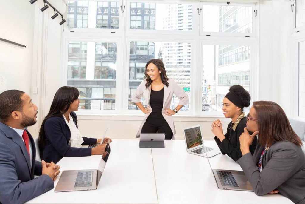 Photo of a group of people smiling during a productive business meeting.