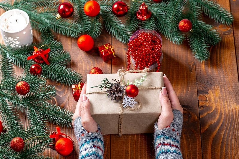 Photo of two hands presenting a wrapped Christmas gift.