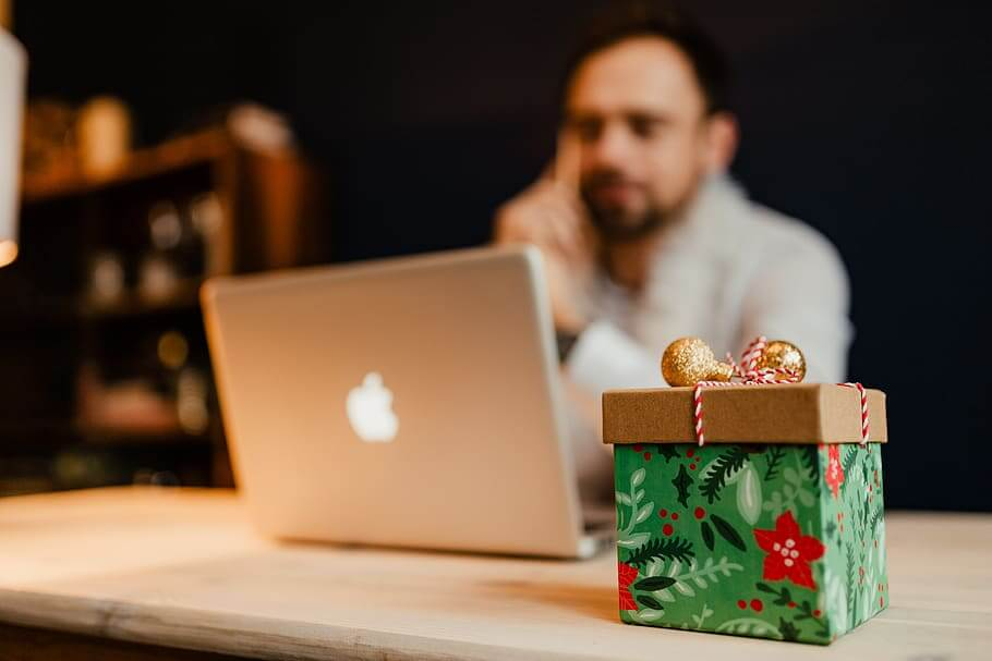 Photo of a man working on Christmas with his computer and a gift sitting in front of him.