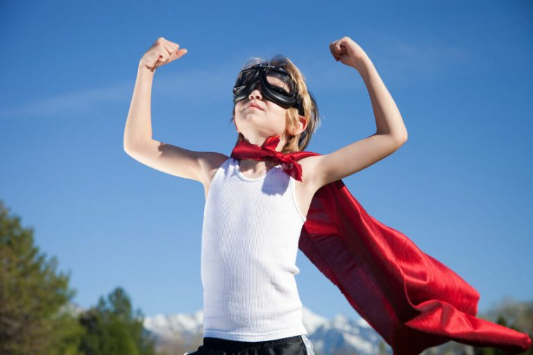Photo of boy in mask and cape flexing his arms with confidence.