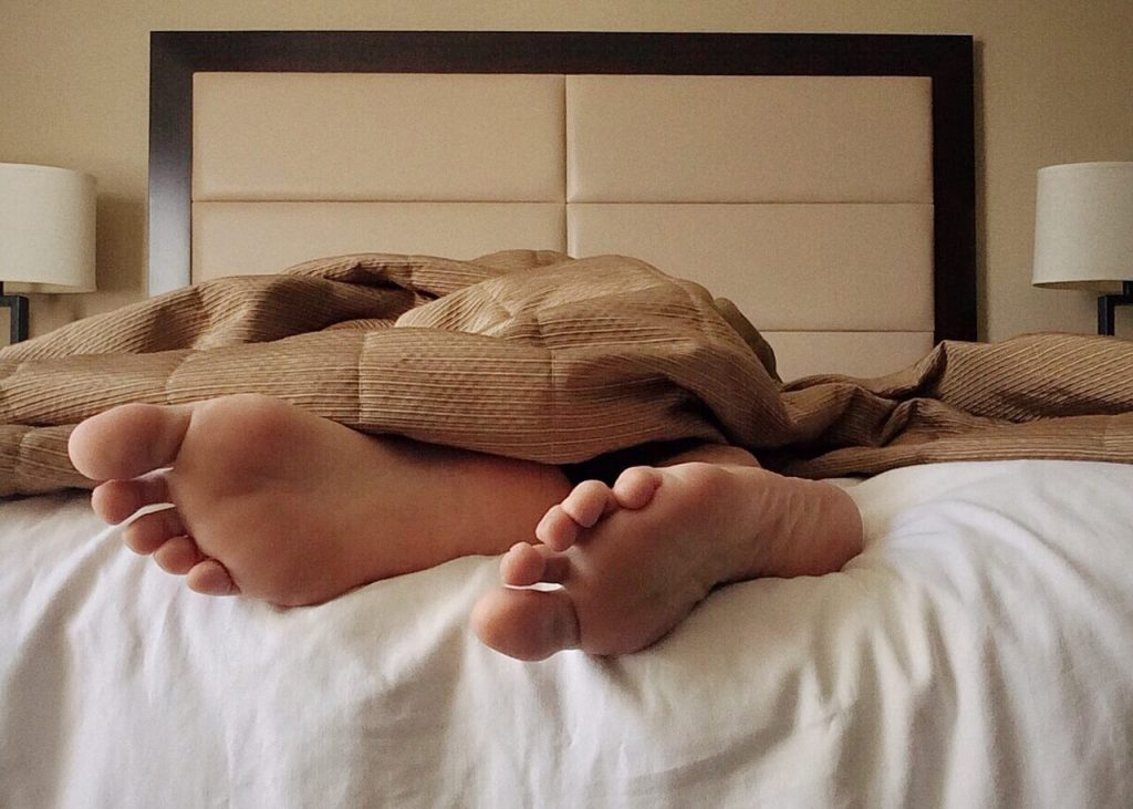 Photo of a blanket and feet protruding at the end of a bed as someone resolves to get more sleep.