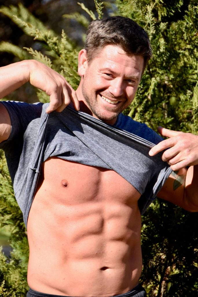 Image of a man holding up his shirt to show his abdominal muscles.