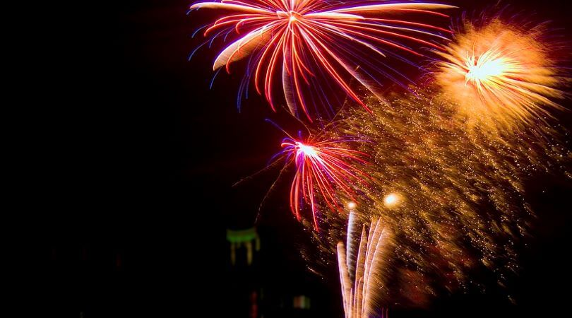 Photo of pink and orange fireworks in a black sky.
