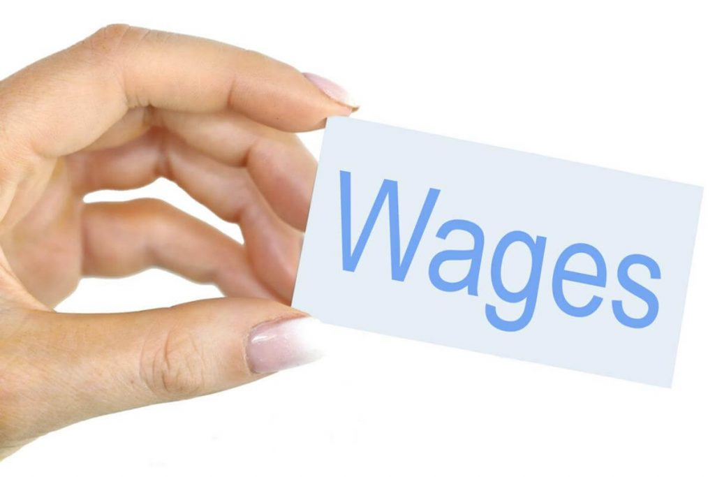 "Image of a hand holding a card that says ""wages."""