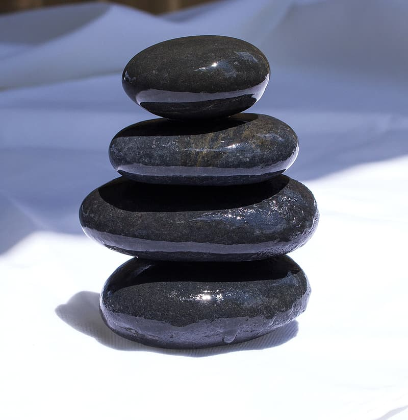 Four black stones balancing on top of one another, symbolizing the four-facto balancing test for joint employer status.
