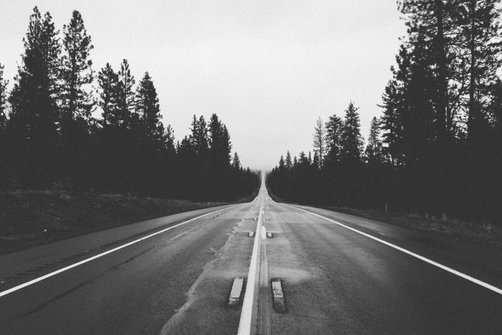 Black and white photo of a long road, putting mileage on a car.