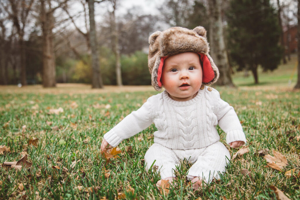 Photo of a baby sitting in the grass with a furry hat on her head.
