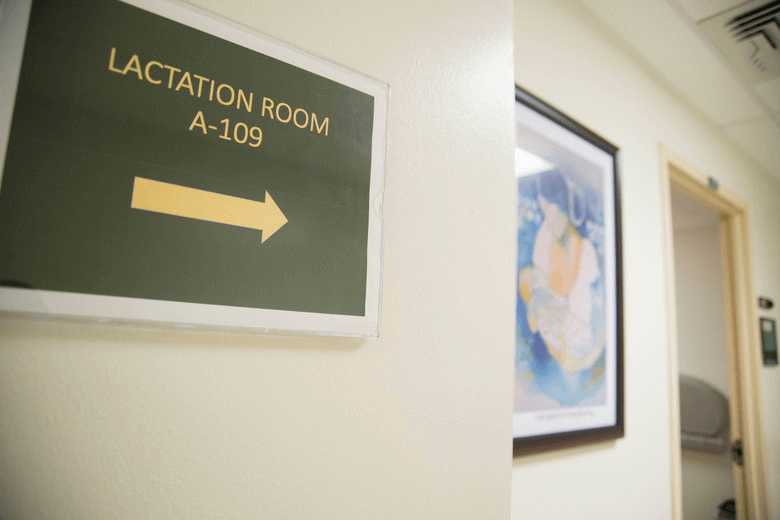 "Photo of a sign that says ""LACTATION ROOM A-109,"" pointing women in the direction of a room where they can breastfeed or express milk."