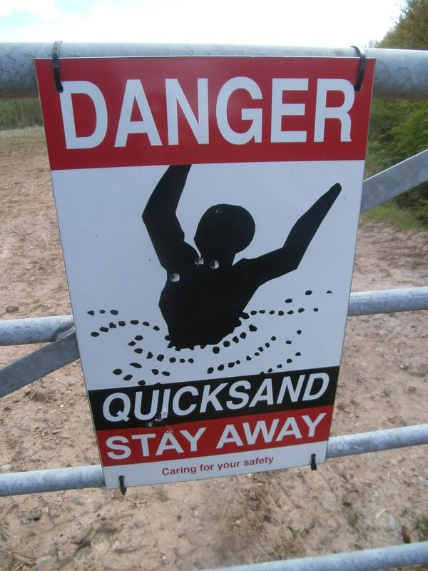 Photo of a DANGER QUICKSAND STAY AWAY sign, meaning to be careful with the new I-9 form.