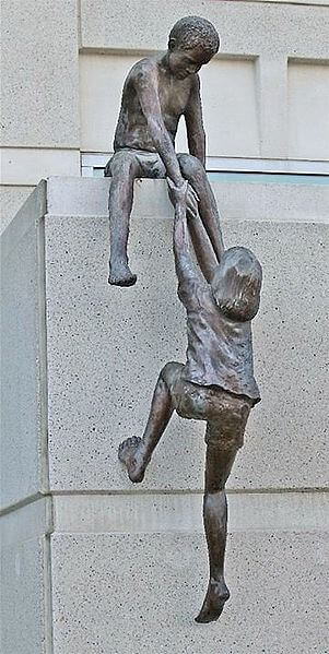 Photo of a sculpture of a little boy extending a helping hand to a little girl to help her up.  This is to symbolize the assistance provided by the Economic Injury Disaster Loan.