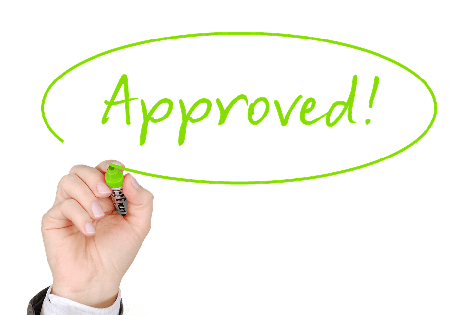 "Image of a hand writing in green marker ""Approved!"" regarding the CARES Act small business disaster loan."