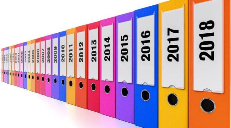 Image of a row of colorful binders with the year printed on the side, organized in consecutive order.