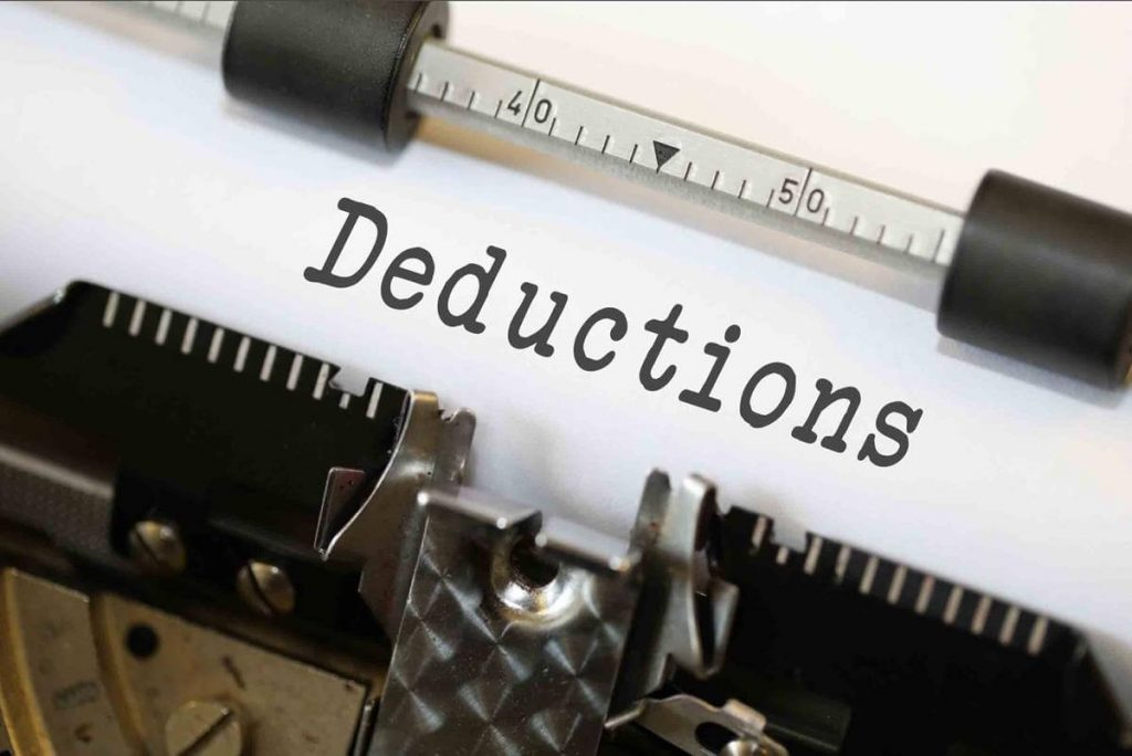 """Image of the word """"Deductions"""" typed using a typewriter, reminding taxpayers to begin organizing for taxes."""