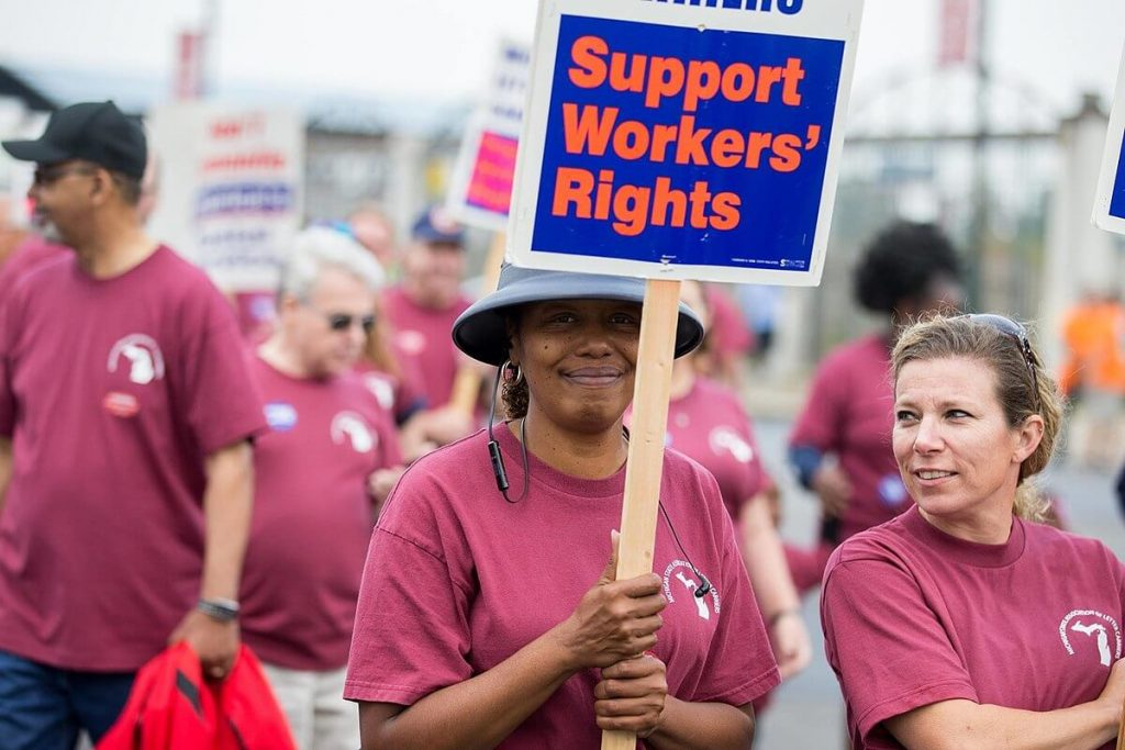 """A woman during a demonstration on Labor Day, holding a sign that says """"support workers' rights"""""""