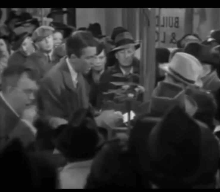 Photo of George Bailey passing out cash at the Bailey Building and Loan in the movie It's a Wonderful Life.
